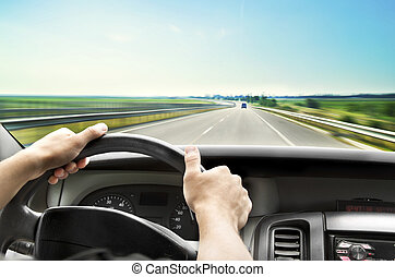 Driving - Mans hands of a driver on steering wheel of a...