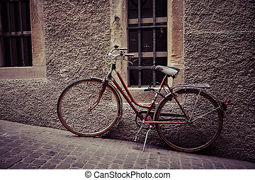 A vintage bicycle resting in the old street (vintage color toned