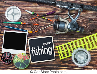 fishing tackle and photoframe on wooden table