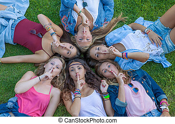 group of teens fingers to lips for suprise secret.