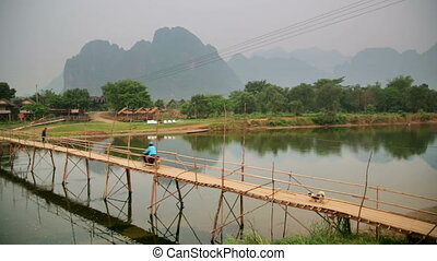 people passing bamboo bridge on limestone mountain...