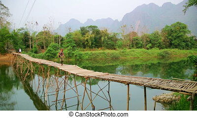 Tourist girl walking on bamboo bridge, vang vieng, laos