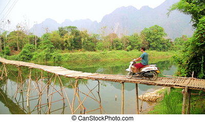 Cheerful Tourist crossing bamboo bridge by motorbike,...