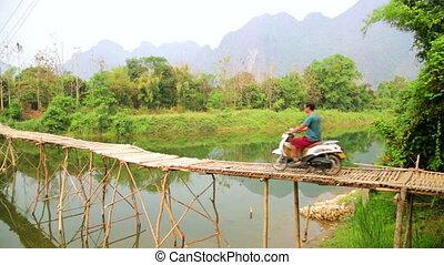 Cheerful Tourist crossing bamboo bridge by motorbike,...