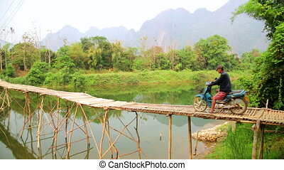 Passing bamboo bridge by motorbike, limestone view, laos