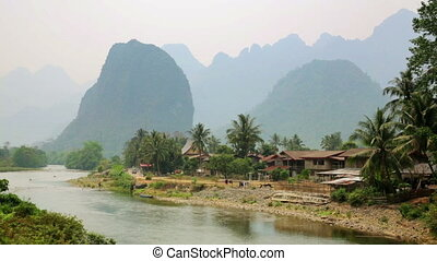 Daily life of Vang Vieng village with limestone mountains,...