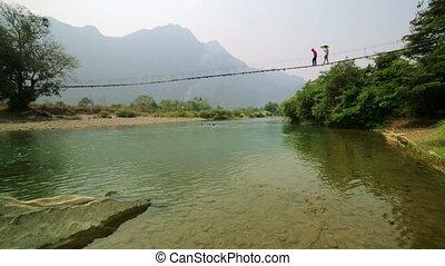 People crossing river on bamboo suspension bridge, vang...