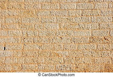 Golden wall built of yellow stone blocks texture