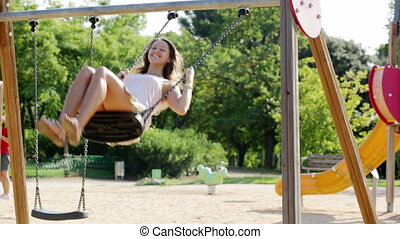 woman in skirt on swing - Young woman in skirt on swing in...
