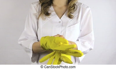 woman robe gloves - Woman in white robe smock put on yellow...