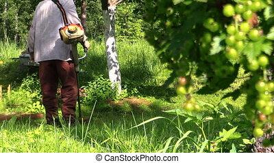 Gardener man cut grass with trimmer near rural well house...