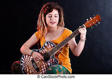 Teenage girl singing and playing guitar - Portrait of a...
