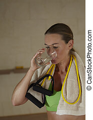 Woman in sports clothing drinking water after workout