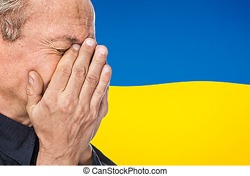 The war in Ukraine. Elderly man covered his face against of...