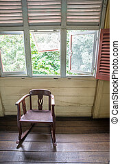 Isolated old rocking chair under several windows in a 19th...