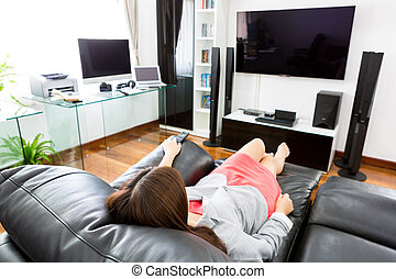 Business young woman watching TV in modern home office with...
