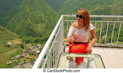 Single attractive woman drinking tea on magnificent mountain...