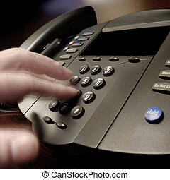 Business Phone Call - Hand diling on a phone in a business...