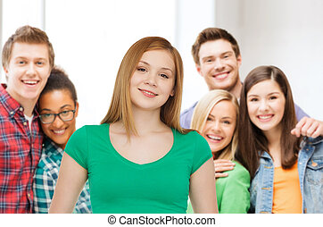 group of smiling teenagers over classroom - friendship,...