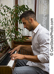 Young handsome male artist playing piano - Young handsome...