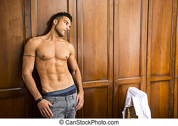 Sexy handsome young man standing shirtless in his bedroom...