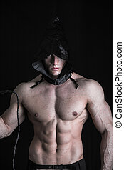 Scary muscular young man with pointed hood on naked body,...