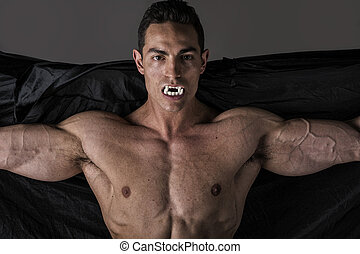 Naked muscular fit young man in briefs posing as a vampire...