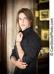 Handsome long hair young man in front of shop window wearing...