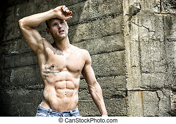 Handsome, muscular young construction worker shirtless...