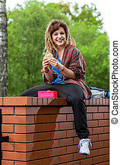 Smiling girl sitting on brick wall and eating lunch