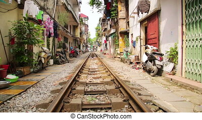 train passing through streets of hanoi slums, vietnam