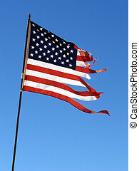 Tattered Flag - US flag in shreds blowing in the strong wind