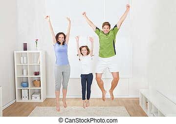 Excited Family In Sportswear Jumping At Home