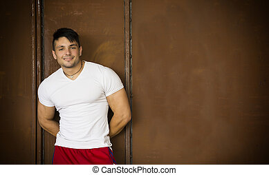 Muscular young man portrait indoors smiling, wearing white...