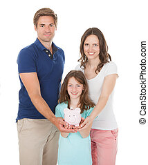 Happy Family Holding Piggy Bank Together - Portrait of happy...