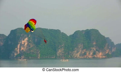 parasailing over limestone mountain islands, Halong Bay,...