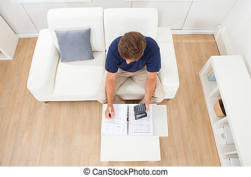 Man Calculating Home Finances At Table - High angle view of...