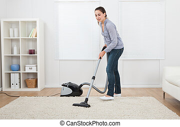 Woman Vacuuming Rug At Home - Full length of young woman...