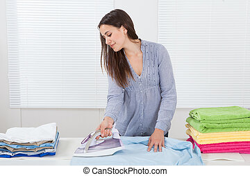 Woman Ironing Clothes In House - Portrait of woman ironing...