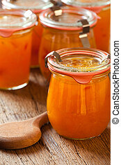 Homemade melon jam in a preserving jar with a wooden spoon...