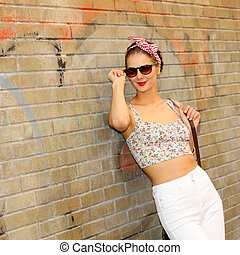 Beautiful stylish emotional brunette in sunglasses posing near brick wall outdoors. Young  woman in the underpass. Lifestyle