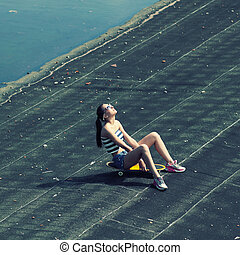 sexy young trendy girl with skateboard posing on the roof