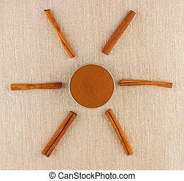 Ground cinnamon in bowl and cinnamon sticks - Ground...