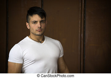 Muscular young man portrait indoors, wearing white t-shirt -...