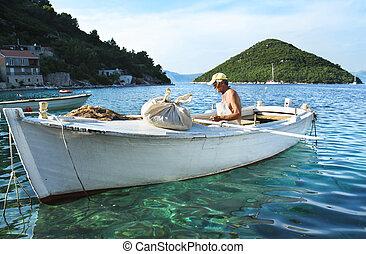 Fisherman in wooden boat, Mljet, Croatia. - MJET, CROATIA -...
