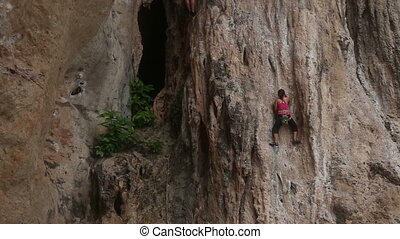 climber climbing a cliff with insurance in tropic