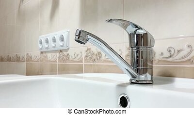 Bathroom faucet - Woman hand opens a water tap in bathroom,...