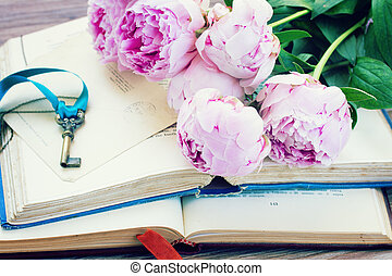 pile of old books with pink flowers