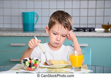 sad little boy sits at the dining table and looking in the...