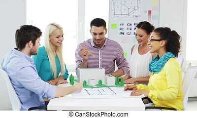 group of smiling architects working in office - startup,...